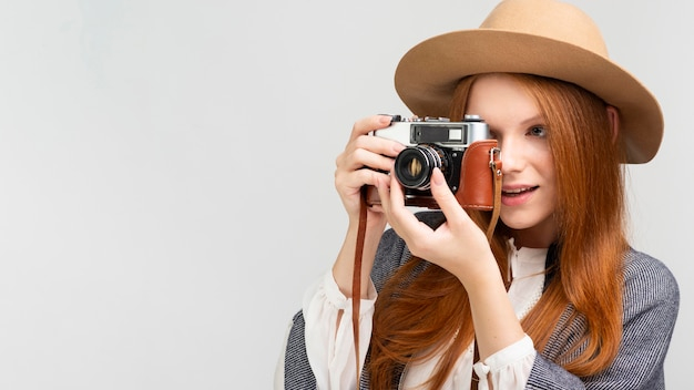 Medium shot woman with camera and hat