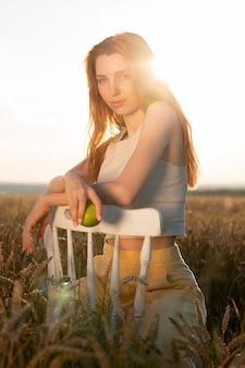 의자를 든 미디엄 샷 여성