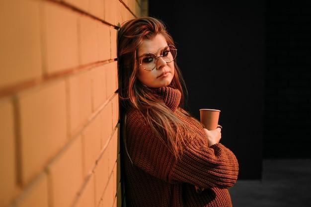 Donna del colpo medio con una tazza di caffè