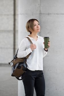 Женщина среднего кадра с кофейной фляжкой