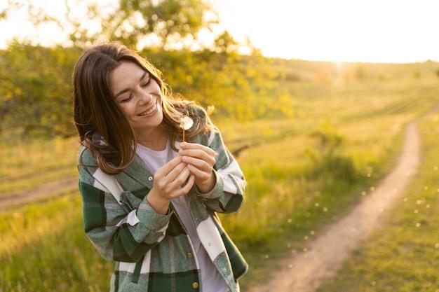 Medium shot woman with dandelion