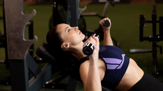 Medium shot woman with dumbbells