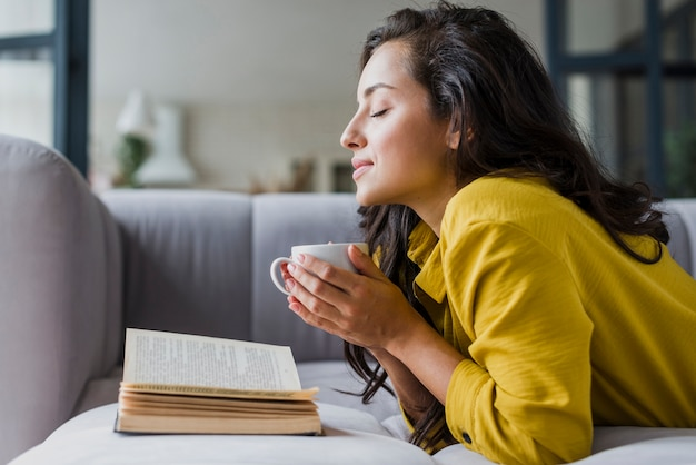 Medium shot woman with eyes closed and book