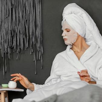 Donna di colpo medio con crema per il viso