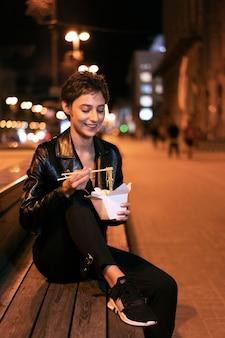 ベンチに食べ物を持つミディアムショットの女性