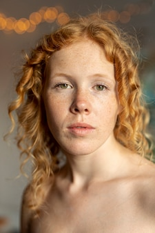 Medium shot woman with freckles posing