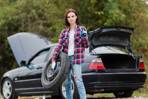 Medium shot of woman with french and tire