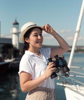 Medium shot woman with hat and binoculars