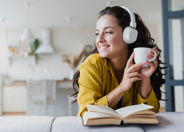 Medium shot woman with headphones and book