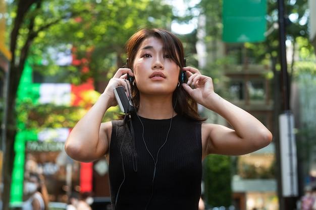 市内のヘッドフォンでミディアムショットの女性