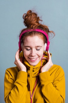 Medium shot woman with headphones and wide smile