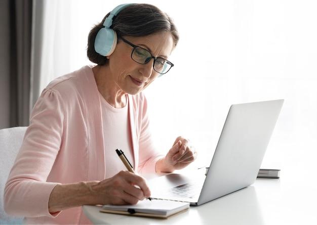 Женщина среднего выстрела с ноутбуком в помещении