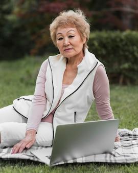 屋外でラップトップを持つミディアムショットの女性