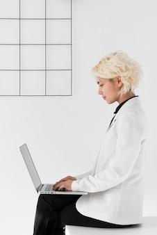 Donna del colpo medio con il computer portatile