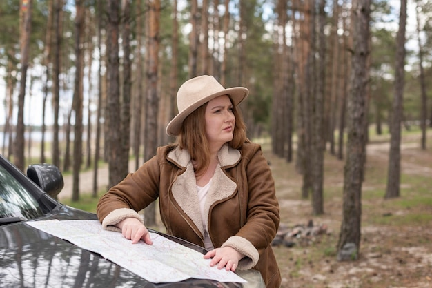 Женщина среднего кадра с картой и автомобилем