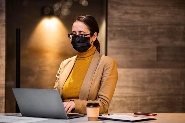 Medium shot woman with mask and laptop