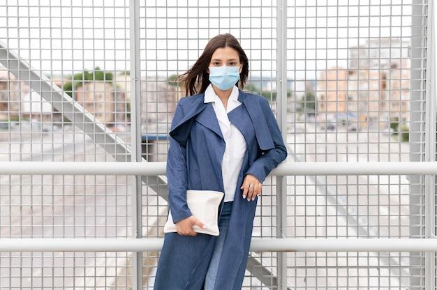 Medium shot woman with mask posing