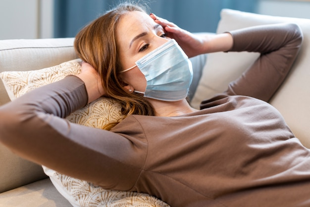 Medium shot woman with mask staying on the couch