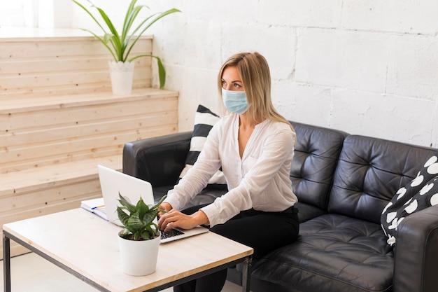 Donna del colpo medio con mascherina medica