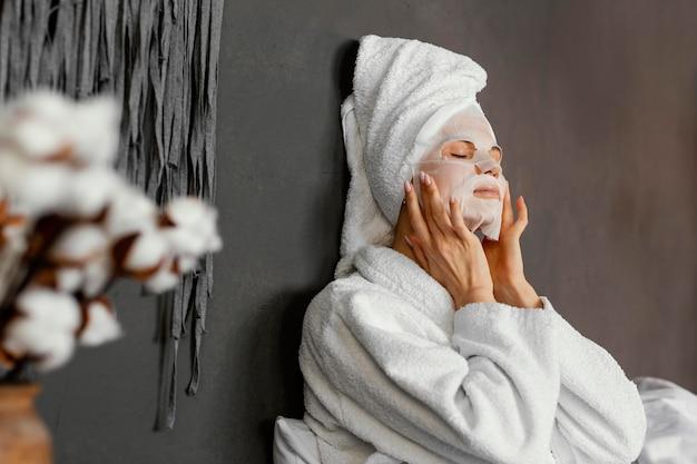 Medium shot woman with moisturizing mask