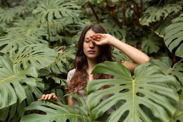 モンステラの葉を持つミディアムショットの女性