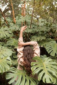 Medium shot woman with monstera plant