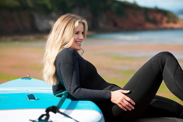 Medium shot woman with paddleboard