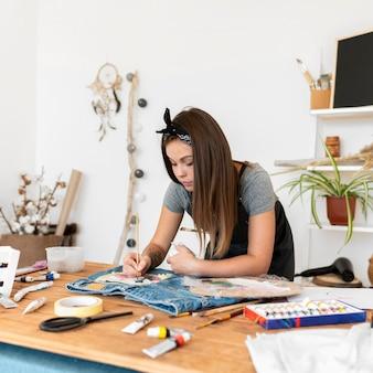 Colpo medio donna con pennello da pittura