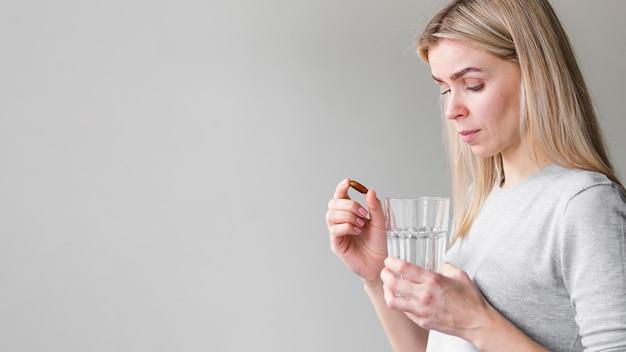 Medium shot woman with pill