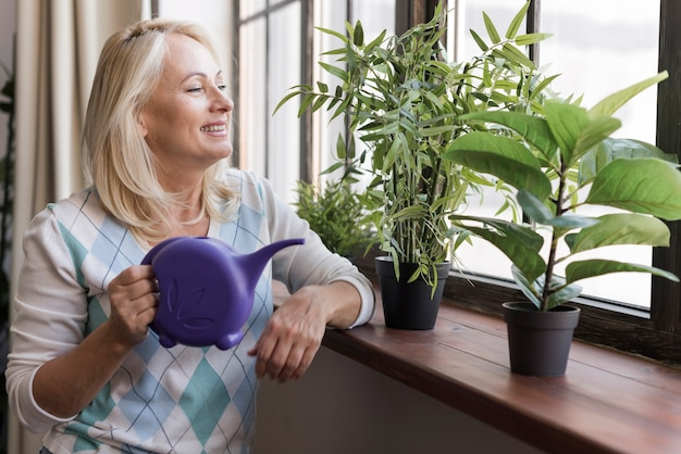 Medium shot woman with purple watering can