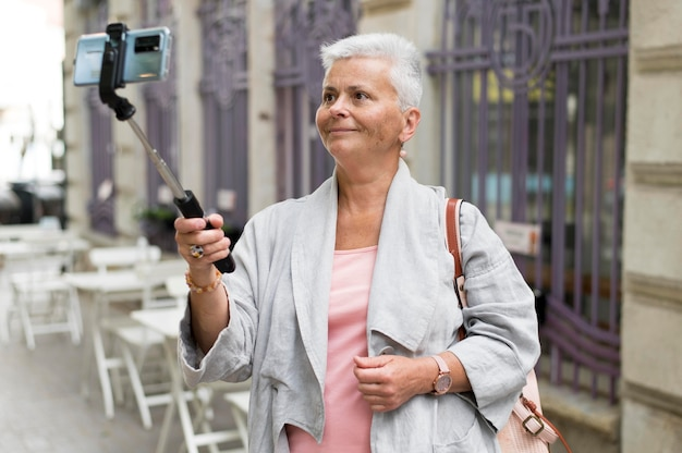 Medium shot woman with selfie stick