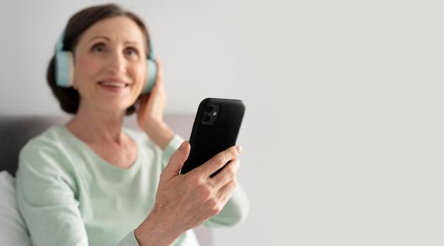 Donna a tiro medio con smartphone