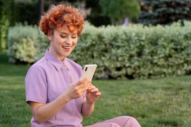 Женщина среднего выстрела со смартфоном