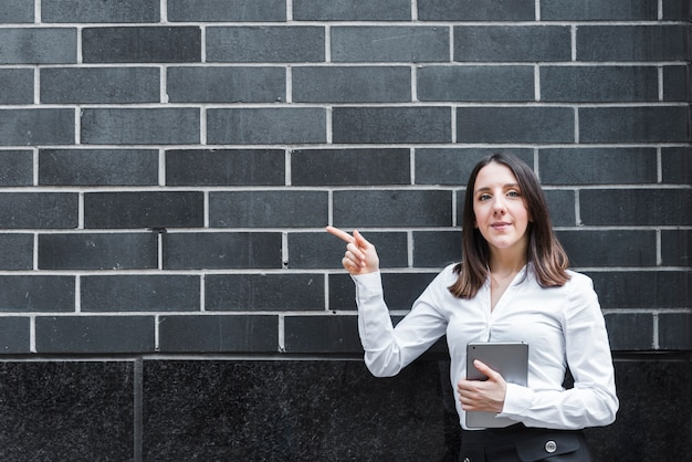 Medium shot woman with tablet pointing at wall