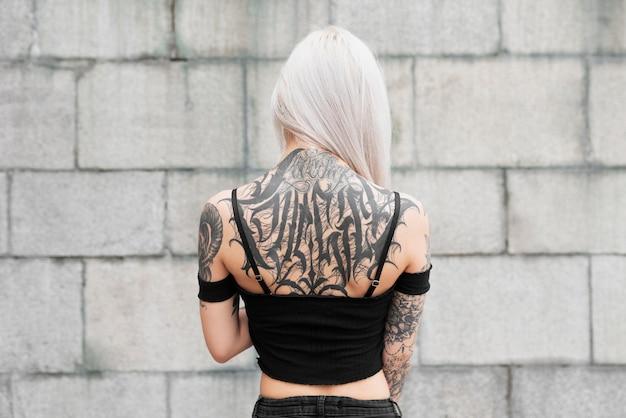 Среднего роста женщина с татуировками на спине