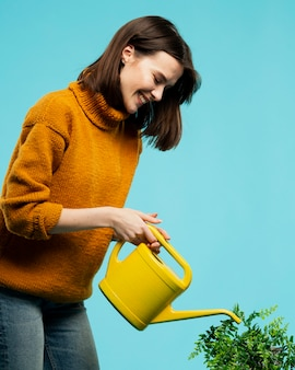 Medium shot of woman with watering can