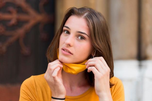 Medium shot woman with yellow mask