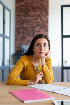 Medium shot of woman wondering while working