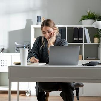 책상에서 일하는 중간 샷 여자