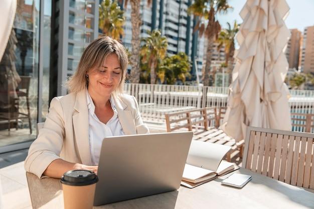 テーブルで働くミディアムショットの女性