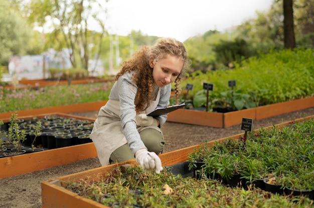 Donna del colpo medio che lavora nel giardino