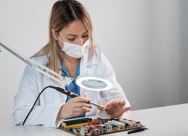기술 분야에서 일하는 중간 샷 여자