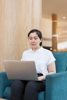 Donna del colpo medio che lavora al computer portatile