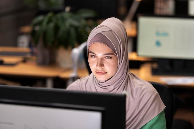 Женщина среднего выстрела, работающая на компьютере