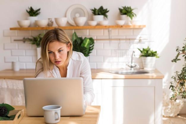 ノートパソコンで作業中のミディアムショットの女性