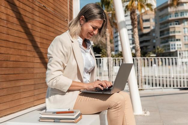 노트북에서 일하는 중간 샷 여자