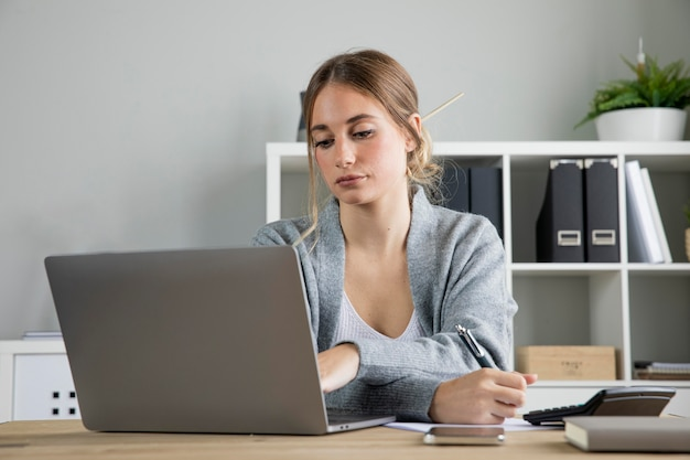 Средний выстрел женщина, работающая на ноутбуке