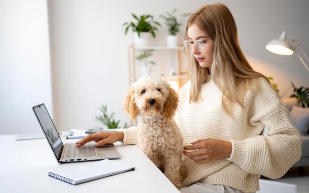 Donna del tiro medio che lavora con un cane carino