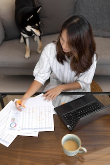 自宅で犬と一緒に働くミディアムショットの女性