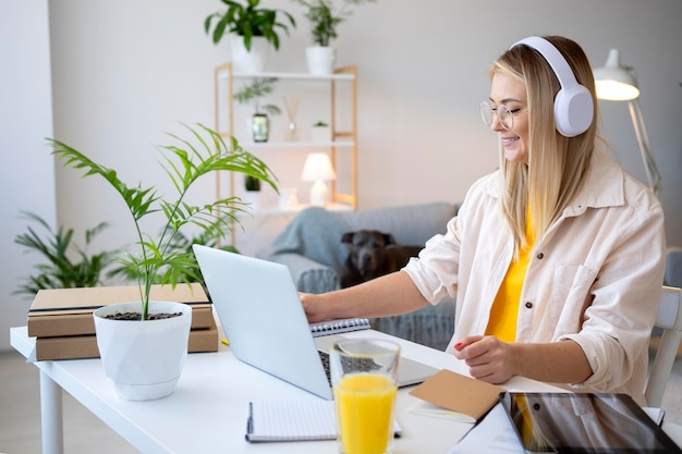 헤드폰으로 작업하는 중간 샷 여성